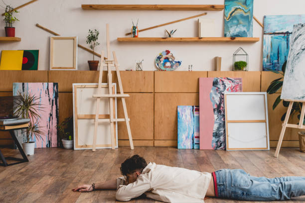 artist laying face down on wooden floor in spacious painting studio - man face down stock pictures, royalty-free photos & images