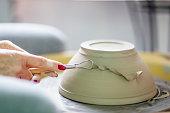 Artist make pot of mug at pottery wheel with hands
