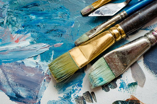 Artist paint brushes on wooden palette. Texture mixed oil paints in different colors. Instruments tools for creative leisure. Painting hobby background. Paintings art concept. Top view. Copy space.