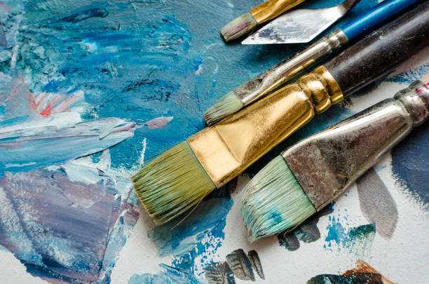 Artist paint brushes on the wooden palette stock photo