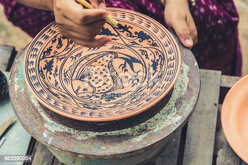 istock Artist paint drawing fish in Sukhothai traditional style pattern with black color in earthenware, making of handcraft pottery in Sukhothai, Thailand. 853390054