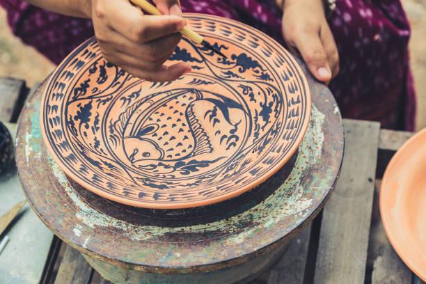 artista pintura desenho peixe sukhothai padrão de estilo tradicional com a cor preta no barro, fazendo do artesanato cerâmica em sukhothai, tailândia. - sukhothai - fotografias e filmes do acervo