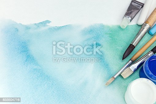 istock artist paintbrushes and paints over abstract green watercolor background on textured paper 833504716