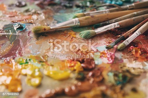 istock Artist paintbrushes over palette with oil colors 577949350