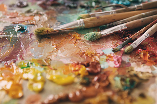 577949148 istock photo Artist paintbrushes over palette with oil colors 577949350