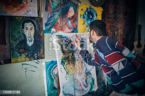 865169666 istock photo Artist- painter working on painting in studio 1203612183