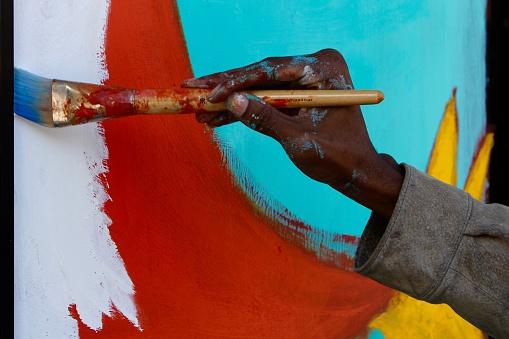 Artist hand painting a mural