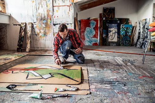 istock Artist Painting Canvas Cardboard On Floor 884992826