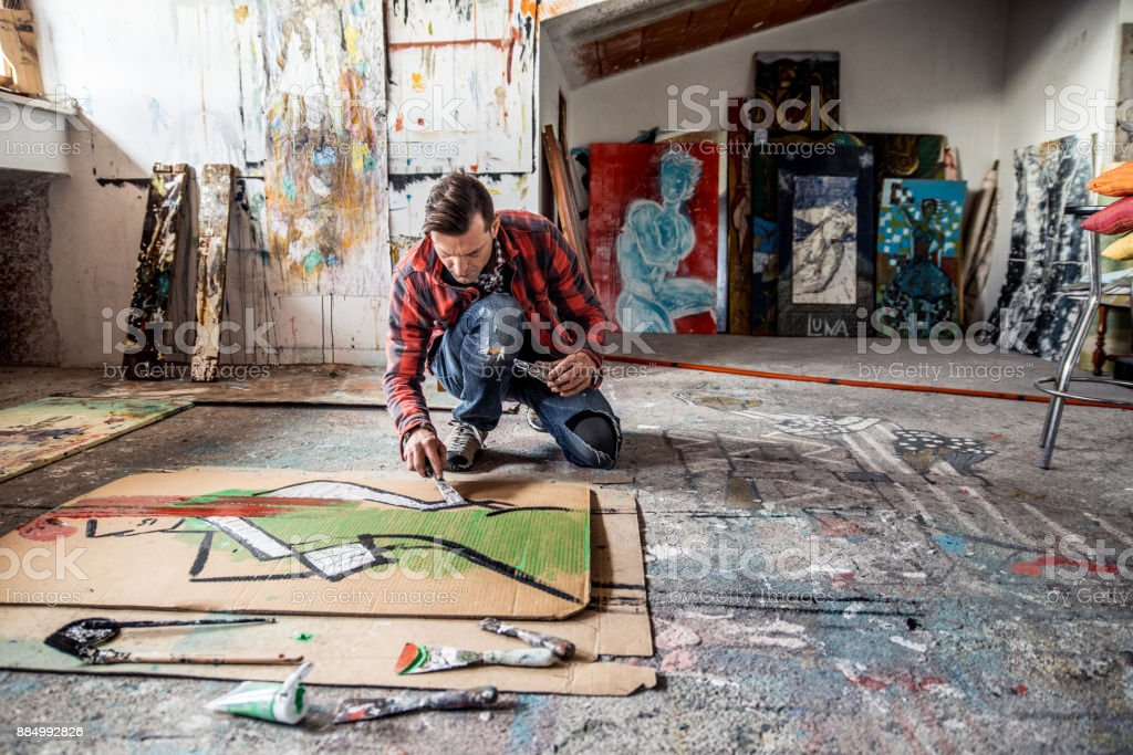 Artist Painting Canvas Cardboard On Floor stock photo