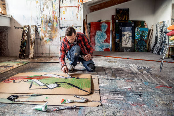 Artist Painting Canvas Cardboard On Floor stock photo