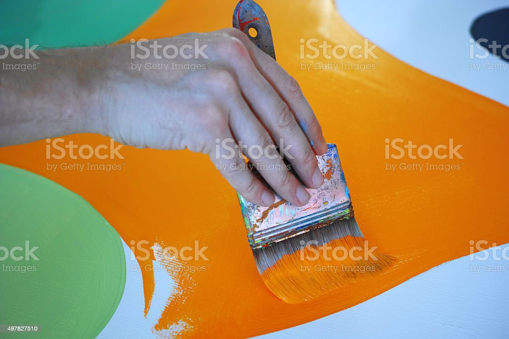Artist Painting Canvas To Orange Colour With Wide Paintbrush stock photo