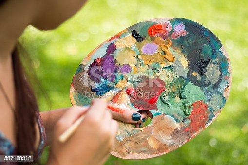 istock Artist painting, holding palette 587188312