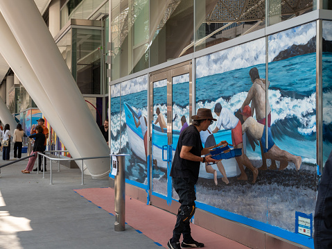 San Francisco, CA AUGUST 11, 2018: Artist painting mural of ocean and boat at Salesforce Transit Center