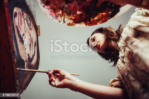 istock Artist painting on a canvas with brush and palette 519620012