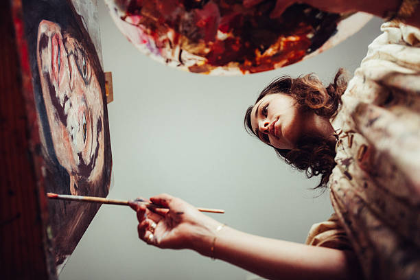 Artist painting on a canvas with brush and palette stock photo