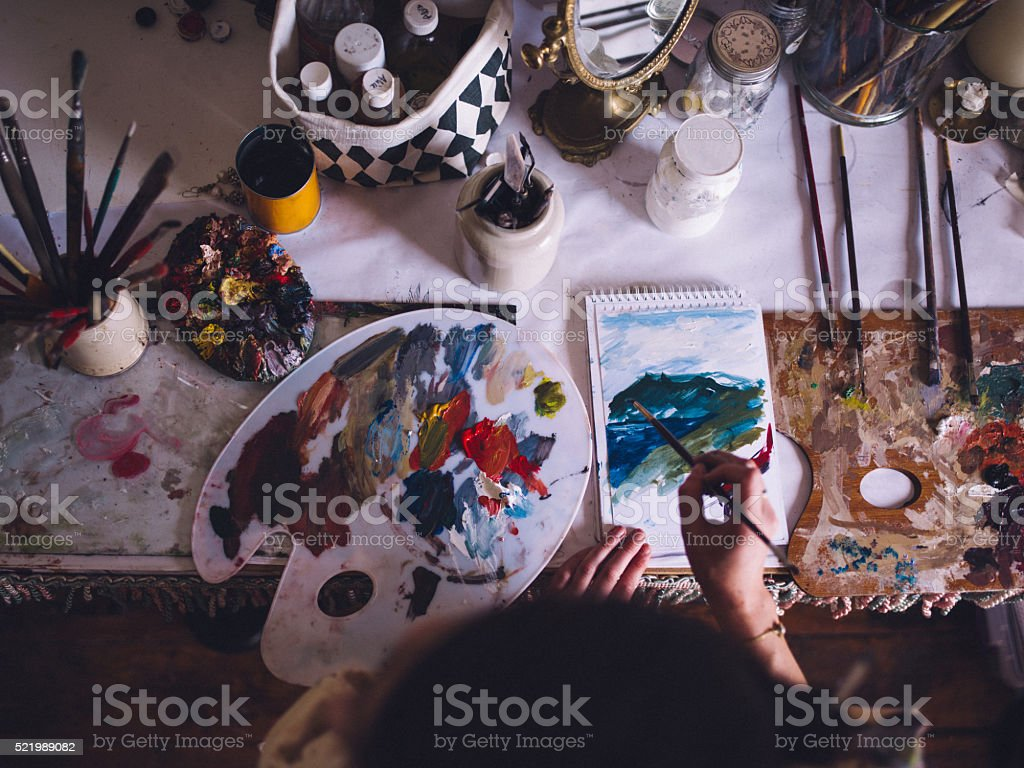 Artist painting on paper with a palette and bright colors stock photo