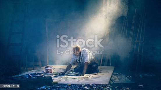 Artist painting picture in workshop rear view. The mature man at studio