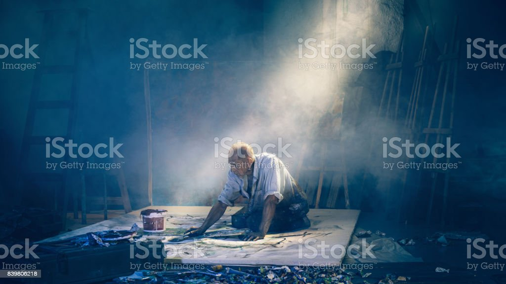 Artist painting picture in workshop rear view stock photo