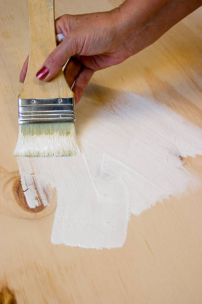 Artist Painting Primer to Board stock photo