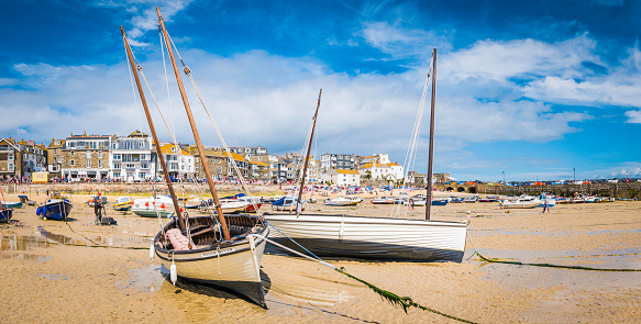 Artist painting wooden boats St Ives harbour beach panorama Cornwall
