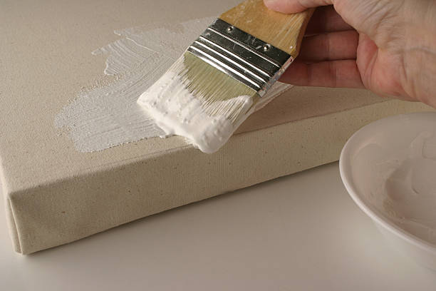 Artist Priming Stretched Canvas with Gesso Paint stock photo