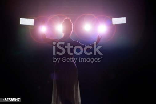 Young women artist (singer or classical dancer) is saluting the public. Rear view from backstage with spotlight in camera lense.