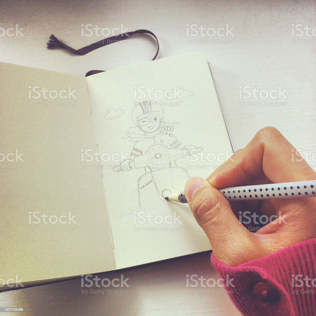 Artist sketching girl and scooter with pencil on sketch book stock photo
