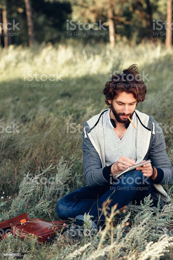 Artist sketching in notebook outdoor, free space stock photo
