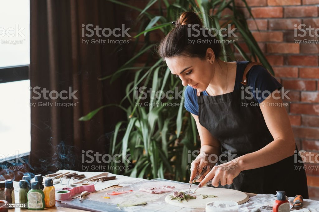 Artist studio. Clay handicraft in process. Young woman with modeling...