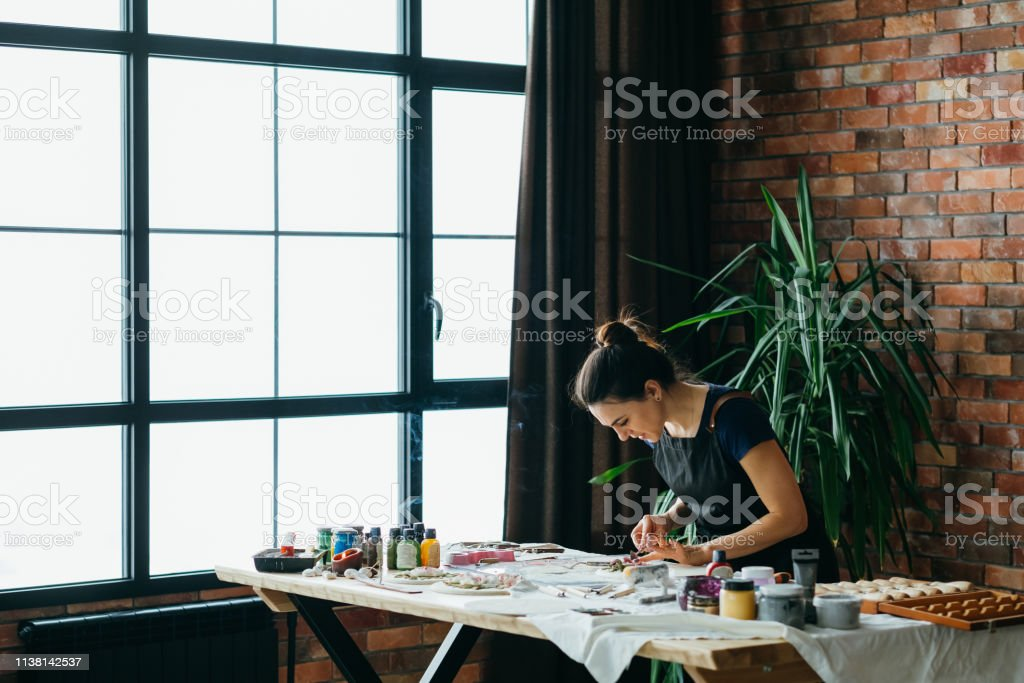 Artist studio. Handicraft artwork in process. Young woman with...