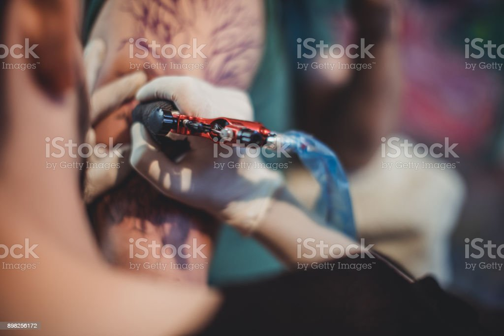 Artist tattooing a man's arm stock photo