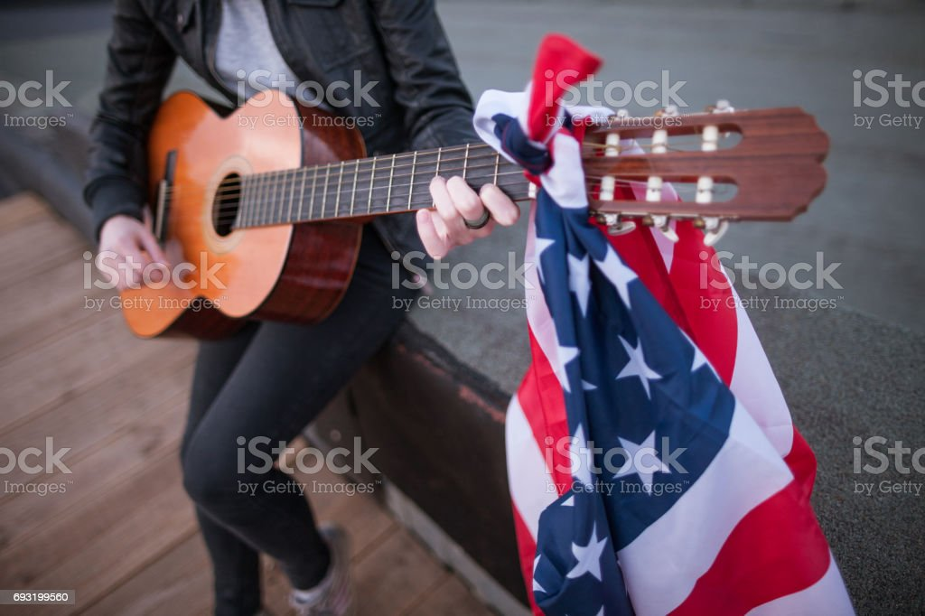 Artist with the US flag playing the guitar stock photo