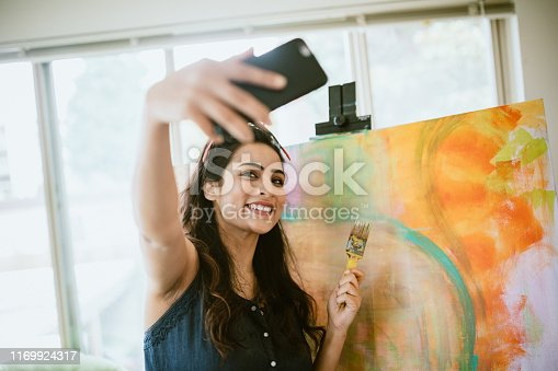 An Indian American woman works on large painted art canvases in the comfort of her apartment living room.