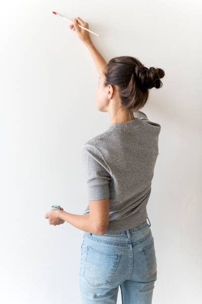 Artist woman painting the wall stock photo