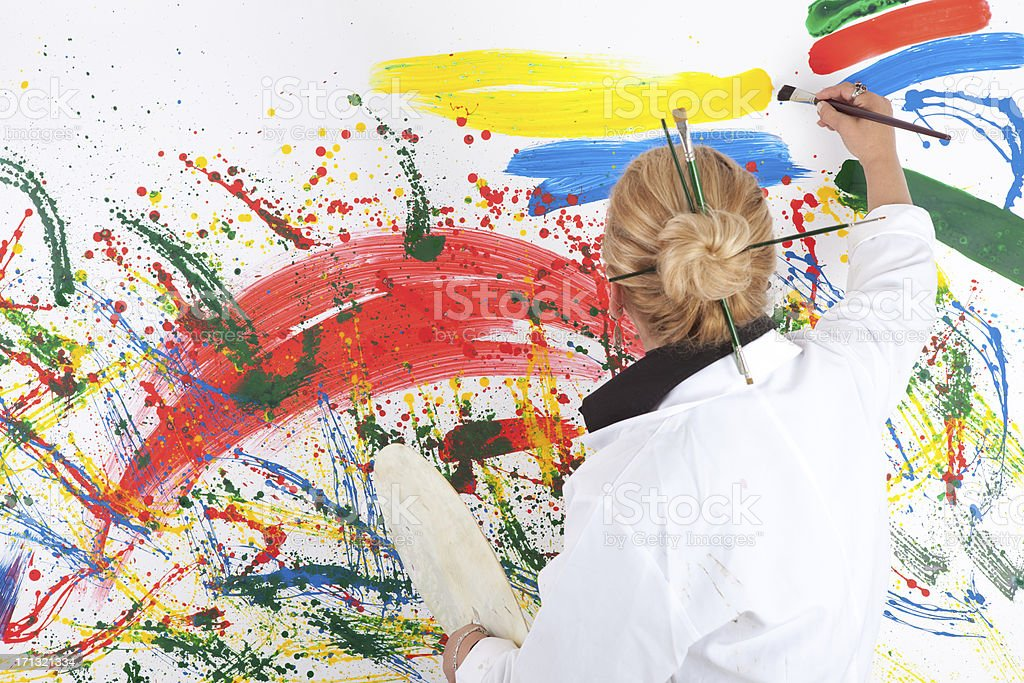 Artist woman standing before painting stock photo