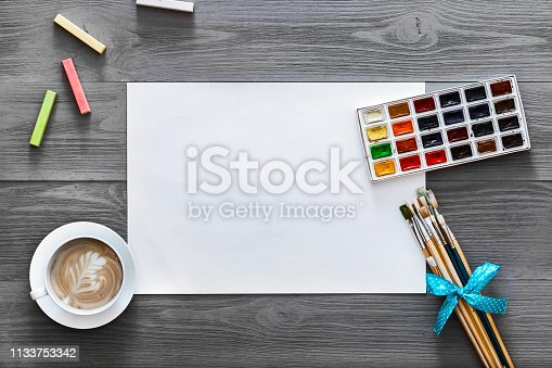 1134879628 istock photo Artist wood gray background concept, creative painting lesson art work supplies paper, paint brushes, paintbox with watercolors coffee on grey wooden table, creativity flat lay top view copy space 1133753342