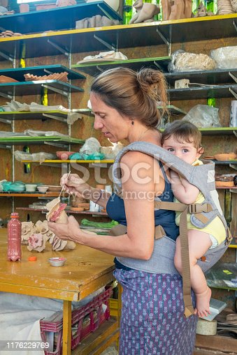 589454570 istock photo Artist working atelier with her daughter on the back 1176229769