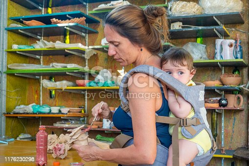 589454570 istock photo Artist working atelier with her daughter on the back 1176230298