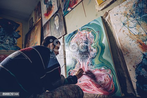865169666 istock photo Artist working on a painting in studio 898826144