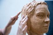 Artist working on clay sculpture in art studio
