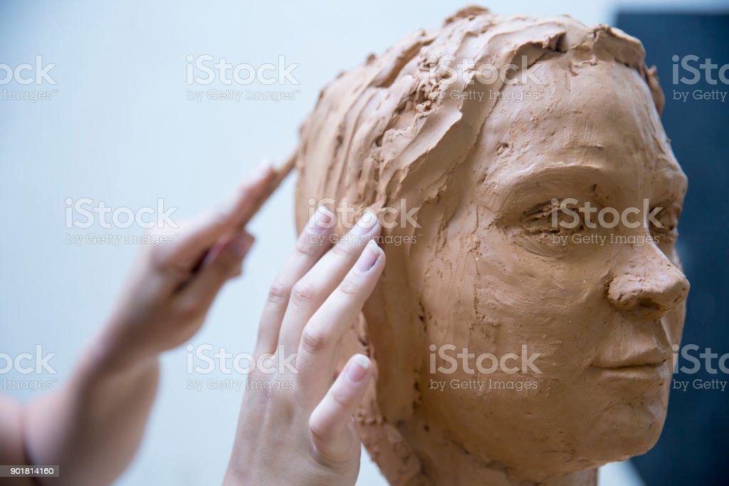 Artist working on clay sculpture in art studio stock photo