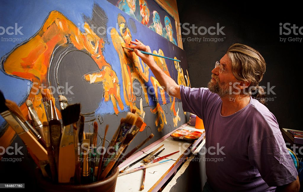 Artist working on large painting with art supplies in front stock photo