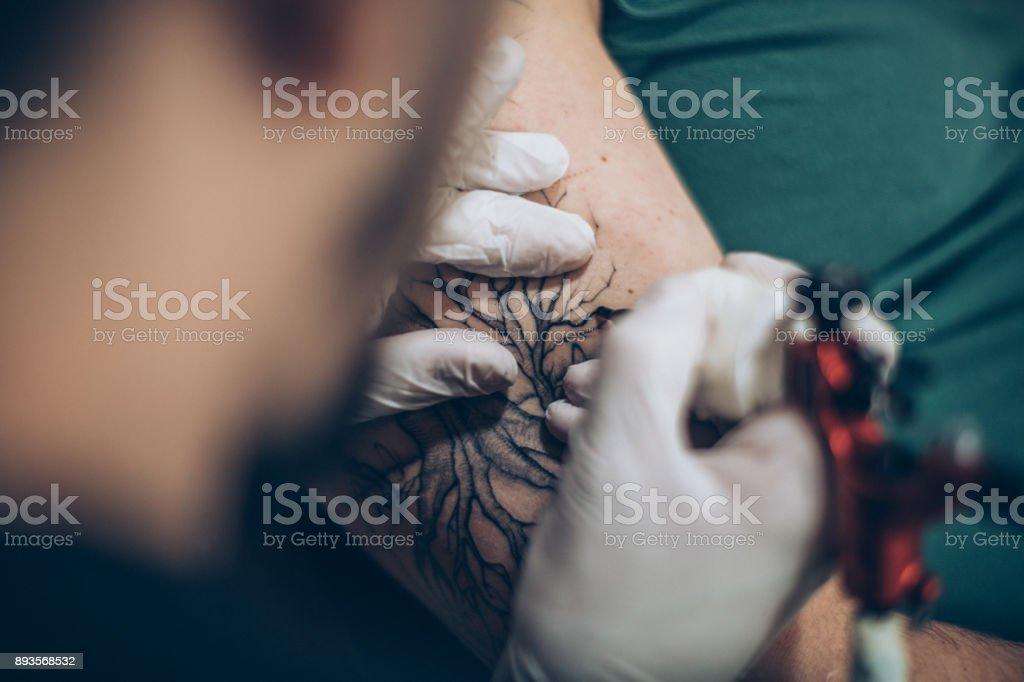 Artist working on tattoo stock photo