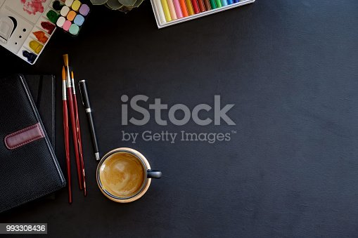 istock Artist workplace with creative craft tools on dark leather desk. 993308436