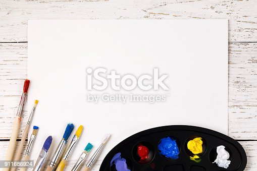 istock Artistic accessories: a palette with paints and tassels for drawing on a wooden table with space for text 911686924
