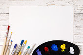 Artistic accessories: a palette with paints and tassels for drawing on a wooden table with space for text