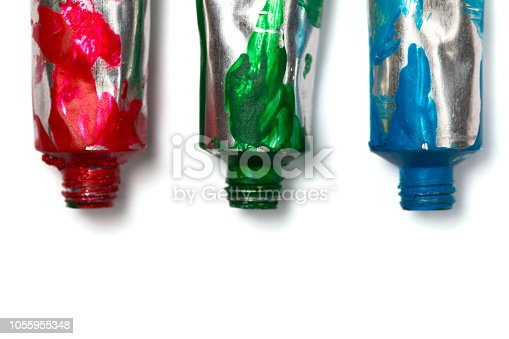 istock Artistic background. Acrylic colourful paint tubes isolated on white background with copy space. Cut out. 1055955348