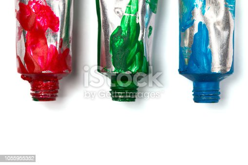 istock Artistic background. Acrylic colourful paint tubes isolated on white background with copy space. Cut out. 1055955352