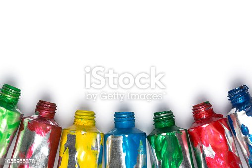 istock Artistic background. Acrylic colourful paint tubes isolated on white background with copy space. Cut out. 1055955378