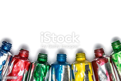 istock Artistic background. Acrylic colourful paint tubes isolated on white background with copy space. Cut out. 1055955392